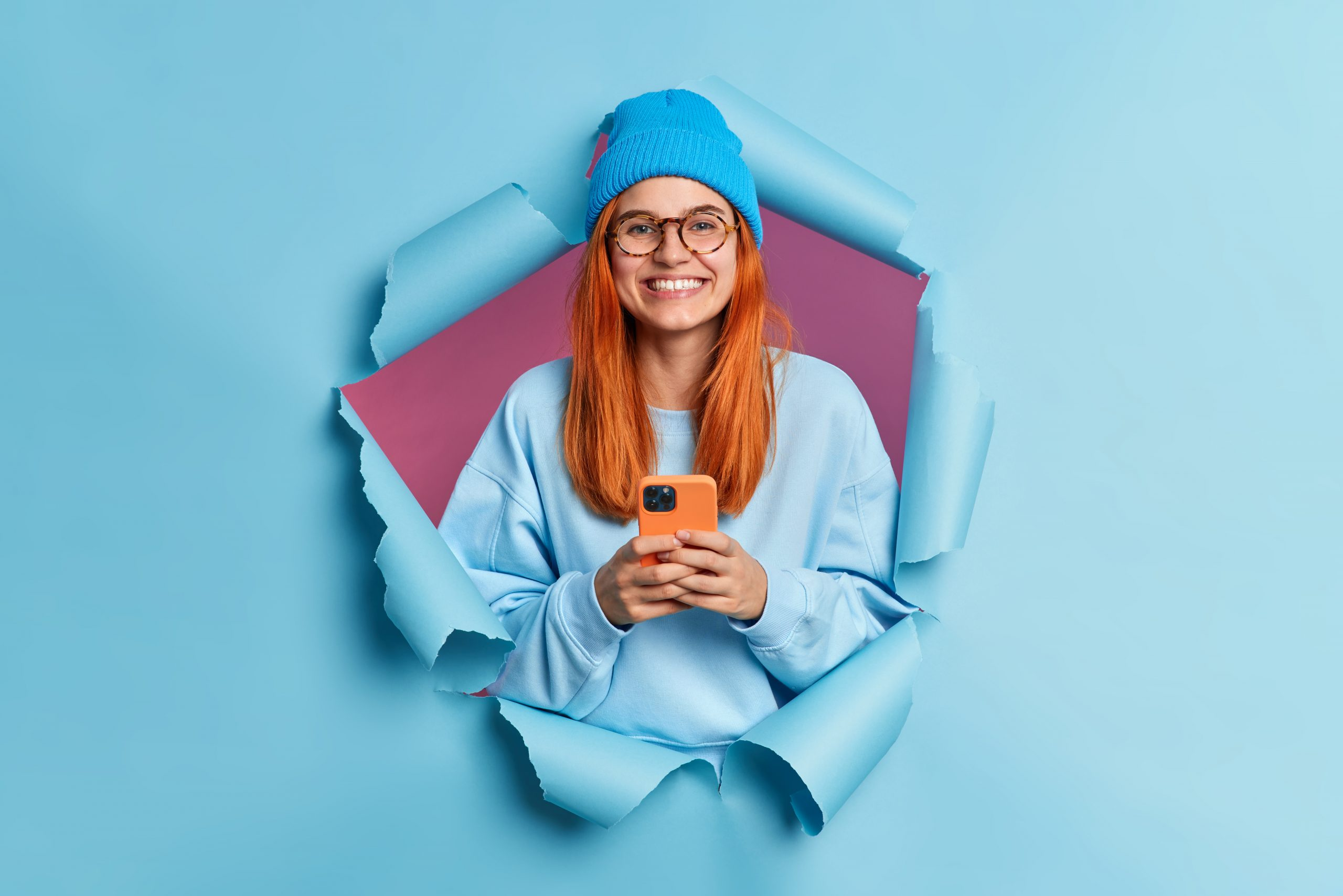 Happy smiling millennial girl with red hair holds modern cellular enjoys texting in social media uses mobile network services wears blue jumper and hat poses in ripped torn paper background.